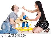 Купить «Молодые родители кормят маленького ребенка на белом фоне. Счастливая семья.», фото № 5540750, снято 24 апреля 2013 г. (c) Мельников Дмитрий / Фотобанк Лори