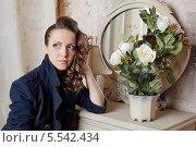 Купить «Молодая женщина в одежде ретро-стиля сидит у старинного столика с зеркалом и горшком цветов», фото № 5542434, снято 26 ноября 2012 г. (c) Losevsky Pavel / Фотобанк Лори
