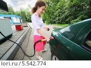 Купить «Молодая красивая женщина улыбаясь заправляет бензином автомобиль на заправке», фото № 5542774, снято 16 июня 2012 г. (c) Losevsky Pavel / Фотобанк Лори