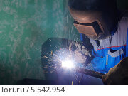 Купить «Сварщик в защитном костюме и маске за работой», фото № 5542954, снято 3 августа 2012 г. (c) Losevsky Pavel / Фотобанк Лори