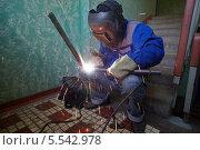 Купить «Сварщик работает в защитном костюме», фото № 5542978, снято 3 августа 2012 г. (c) Losevsky Pavel / Фотобанк Лори