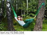 Купить «Молодая женщина в темных очках лежит в гамаке, натянутом между двумя толстыми березами, закинув руки за голову», фото № 5543334, снято 7 августа 2012 г. (c) Losevsky Pavel / Фотобанк Лори