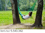 Купить «Молодая женщина лежит в гамаке, натянутом между двумя толстыми березами», фото № 5543342, снято 7 августа 2012 г. (c) Losevsky Pavel / Фотобанк Лори