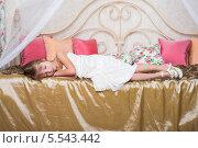 Купить «Маленькая девочка спит на кровати в одежде и обуви», фото № 5543442, снято 3 декабря 2012 г. (c) Losevsky Pavel / Фотобанк Лори