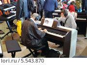 Купить «Люди играют на электронных пианино установках с наушниками на XVIII Международной выставке музыки в Сокольниках 22 сентября 2012 в Москве, Россия», фото № 5543870, снято 22 сентября 2012 г. (c) Losevsky Pavel / Фотобанк Лори