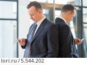 Бизнесмен в костюме и галстуке с мобильным телефоном стоит спиной к зеркалу. Стоковое фото, фотограф Losevsky Pavel / Фотобанк Лори