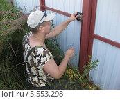 Мужчина чинит замок на воротах. Стоковое фото, фотограф Склярова Ирина / Фотобанк Лори
