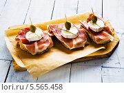 Купить «бутерброды с козьим сыром и ветчиной лежат на доске», фото № 5565458, снято 10 апреля 2013 г. (c) Food And Drink Photos / Фотобанк Лори
