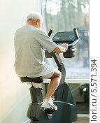 Купить «Пожилой мужчина занимается на велотренажере в фитнес-клубе», фото № 5571394, снято 18 января 2014 г. (c) Andrejs Pidjass / Фотобанк Лори