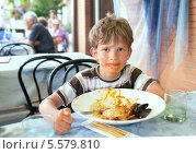 Купить «Мальчик ест блюдо из морепродуктов», фото № 5579810, снято 10 июля 2012 г. (c) Юлия Кузнецова / Фотобанк Лори