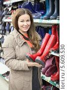 Купить «Довольная молодая женщина с красными резиновыми сапогами в руках», фото № 5609530, снято 14 февраля 2014 г. (c) Кекяляйнен Андрей / Фотобанк Лори