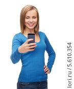 Купить «Жизнерадостная девушка в голубом свитере рассматривает современный телефон», фото № 5610354, снято 5 декабря 2013 г. (c) Syda Productions / Фотобанк Лори