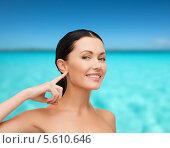Купить «Милая брюнетка указывает на свое ухо на фоне моря», фото № 5610646, снято 1 декабря 2013 г. (c) Syda Productions / Фотобанк Лори
