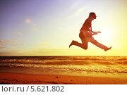 Купить «Силуэт танцора, прыгающего высоко вверх на фоне заката над морем», фото № 5621802, снято 8 февраля 2011 г. (c) Sergey Nivens / Фотобанк Лори