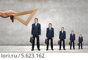 Купить «Рука измеряет линейкой самого высокого бизнесмена в ряду коллег», фото № 5623162, снято 17 июня 2019 г. (c) Sergey Nivens / Фотобанк Лори