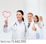 Купить «Улыбающаяся доктор рисует в воздухе сердце на фоне своих коллег», фото № 5642050, снято 1 декабря 2013 г. (c) Syda Productions / Фотобанк Лори
