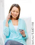 Счастливая девушка сообщает детали банковской карты по телефону. Стоковое фото, фотограф Syda Productions / Фотобанк Лори