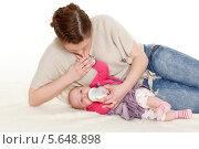 Купить «Молодая мама кормит ребенка из бутылочки молочной смесью на белом фоне. Прикорм. Счастливая семья.», фото № 5648898, снято 9 января 2014 г. (c) Мельников Дмитрий / Фотобанк Лори