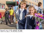 Купить «Брат и сестра с цветами у крыльца школы 1 сентября», фото № 5650538, снято 1 сентября 2012 г. (c) Losevsky Pavel / Фотобанк Лори
