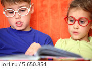 Купить «Мальчик и девочка в очках читают книгу», фото № 5650854, снято 19 октября 2011 г. (c) Losevsky Pavel / Фотобанк Лори