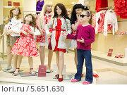 Девочка стоит у группы манекенов в магазине. Стоковое фото, фотограф Losevsky Pavel / Фотобанк Лори