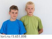 Купить «Портрет двух улыбающихся мальчиков в цветных футболках на фоне белой стены», фото № 5651898, снято 7 июля 2012 г. (c) Losevsky Pavel / Фотобанк Лори