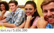 Купить «Students sitting in a line smiling at camera», видеоролик № 5656390, снято 29 марта 2020 г. (c) Wavebreak Media / Фотобанк Лори