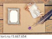 Рамка для фотографии, фигурка ангела и перо для письма на столе. Стоковое фото, фотограф Anhelina Tarasenko / Фотобанк Лори