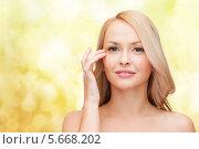 Купить «Красивая девушка показывает пальцем на кожу вокруг глаз», фото № 5668202, снято 7 января 2014 г. (c) Syda Productions / Фотобанк Лори