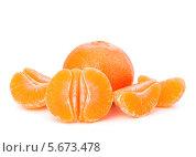 Купить «Неочищенный мандарин и мандариновые дольки на белом фоне», фото № 5673478, снято 27 декабря 2011 г. (c) Natalja Stotika / Фотобанк Лори