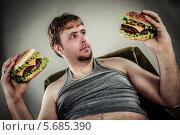 Купить «Толстый мужчина с двумя гамбургерами в руках сидит в кресле», фото № 5685390, снято 3 апреля 2012 г. (c) Андрей Армягов / Фотобанк Лори