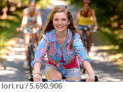 Купить «Девочка-подросток катается на велосипеде с друзьями в парке», фото № 5690906, снято 1 августа 2013 г. (c) CandyBox Images / Фотобанк Лори