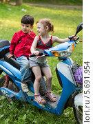 Купить «Два ребенка сидят на голубом скутере на природе», фото № 5691954, снято 2 июня 2013 г. (c) Losevsky Pavel / Фотобанк Лори