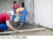 Купить «Трое рабочих в спецодежде заливают пол специальным раствором», фото № 5692066, снято 3 июля 2013 г. (c) Losevsky Pavel / Фотобанк Лори