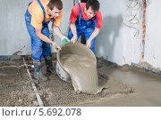 Купить «Двое рабочих в комбинезонах заливают пол цементом», фото № 5692078, снято 3 июля 2013 г. (c) Losevsky Pavel / Фотобанк Лори
