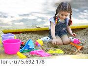 Купить «Маленькая девочка с косичками сидит на песке в песочнице и играет с формочками», фото № 5692178, снято 4 июня 2013 г. (c) Losevsky Pavel / Фотобанк Лори