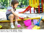 Купить «Маленькая девочка с косичками сидит в песочнице и играет с формочками», фото № 5692182, снято 4 июня 2013 г. (c) Losevsky Pavel / Фотобанк Лори