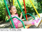 Купить «Счастливая маленькая девочка с длинными темными волосами сидит на качелях на детской площадке», фото № 5692206, снято 4 июня 2013 г. (c) Losevsky Pavel / Фотобанк Лори