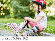 Купить «Девочка надевает ролики в парке», фото № 5692362, снято 4 июля 2013 г. (c) Losevsky Pavel / Фотобанк Лори