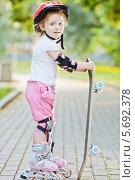 Купить «Маленькая девочка на роликах со скейтбордом в парке», фото № 5692378, снято 4 июля 2013 г. (c) Losevsky Pavel / Фотобанк Лори
