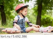 Купить «Маленькая девочка в шлеме и защите сидит в роликах на асфальте», фото № 5692386, снято 4 июля 2013 г. (c) Losevsky Pavel / Фотобанк Лори