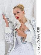 Купить «Красивая молодая блондинка в белом платье и светлой шубе позирует с украшением в руках, сидя на ледяном троне на фоне ледяной стены», фото № 5692438, снято 3 октября 2013 г. (c) Losevsky Pavel / Фотобанк Лори