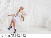 Купить «Красивая блондинка в белом платье, светлой пушистой шубе и синих туфлях на высоком каблуке сидит на ледяном троне в студии на фоне ледяной стены», фото № 5692442, снято 3 октября 2013 г. (c) Losevsky Pavel / Фотобанк Лори