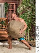Купить «Мускулистый мужчина поднял большой камень на песчаном пляже», фото № 5692554, снято 3 октября 2013 г. (c) Losevsky Pavel / Фотобанк Лори