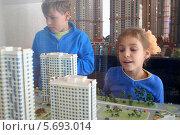Купить «Мальчик и девочка смотрят на макет жилого комплекса», фото № 5693014, снято 26 июля 2013 г. (c) Losevsky Pavel / Фотобанк Лори