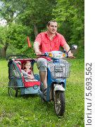 Купить «Папа на скутере с прицепленной коляской с детьми», фото № 5693562, снято 2 июня 2013 г. (c) Losevsky Pavel / Фотобанк Лори