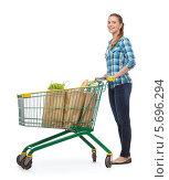 Купить «Симпатичная девушка в повседневной одежде с покупками в тележке на белом фоне», фото № 5696294, снято 12 февраля 2014 г. (c) Syda Productions / Фотобанк Лори
