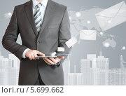 Купить «Бизнесмен в костюме с планшетным компьютером в руках», иллюстрация № 5699662 (c) Кирилл Черезов / Фотобанк Лори