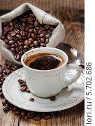Купить «Чашка кофе и мешочек с кофейными зернами на деревянном столе», фото № 5702686, снято 22 сентября 2018 г. (c) BE&W Photo / Фотобанк Лори