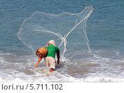 Купить «Рыбак забрасывает невод в море», эксклюзивное фото № 5711102, снято 21 февраля 2014 г. (c) Александр Тарасенков / Фотобанк Лори